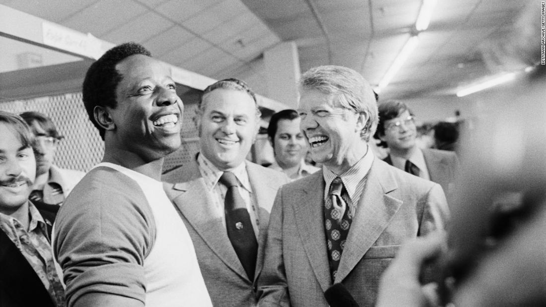 Future US President Jimmy Carter, then the governor of Georgia, laughs with Aaron during a clubhouse visit in 1973.