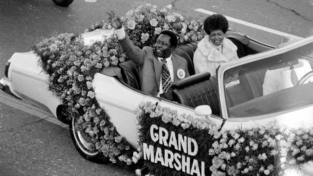Aaron waves to the crowd as grand marshal of the Tournament of Roses parade in Pasadena, 加利福尼亚州, 在 1975. Riding with him in the car is his second wife, Billye.