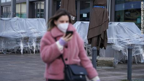 A woman wearing an FFP2 face mask walks past a shuttered cafe in Berlin, 독일.
