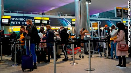 Passengers queue at a check-in desk at Heathrow Airport in London on December 21.