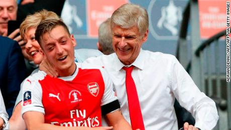 Ozil celebrates winning the FA Cup in 2017 alongside former Arsenal manager Arsene Wenger.