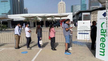 24 جنوری 2021 کو لوگ دبئی کے مالیاتی مرکز ضلع میں ایک ویکسینیشن کی سہولت پر قطار میں کھڑے ہیں۔