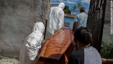 Municipal workers from SOS Funeral remove the body of 75-year-old Adamor Mendonca Maciel from his home in Manaus on January 16, 2021 after he died of COVID-19.