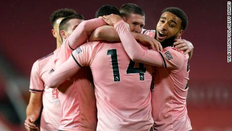 Burke celebrates with Jayden Bogle and team mates after scoring their side's second goal.
