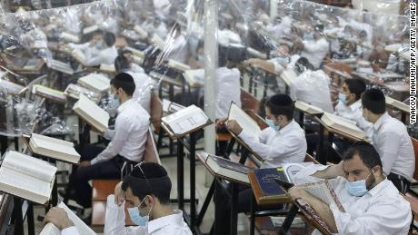 Ultra-Orthodox Jewish men study in a hall divided with plastic sheets to protect against Covid-19 in Bnei Brak on October 25, 2020.