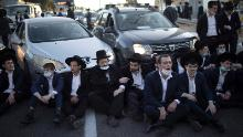Ultra-Orthodox Jews block a road in Bnei Brak during a demonstration staged moments before Israel entered a third nationwide lockdown on December 27.