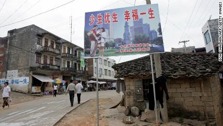 "A one-child policy billboard saying, ""Have less children, have a better life"" greets residents on the main street of Shuangwang in southern China in 2007."