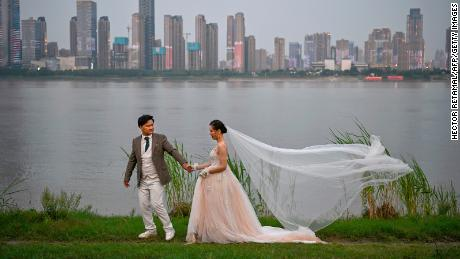 A couple poses during a wedding photo shoot next to Yangtze River in Wuhan, China.