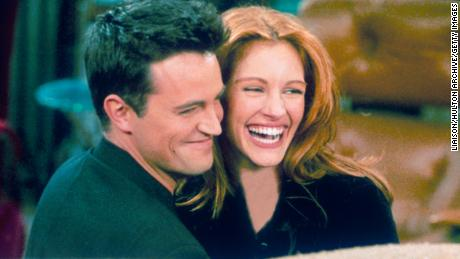 "Matthew Perry and Julia Roberts hug on the set of ""Friends."""