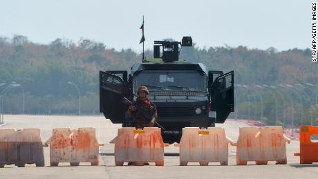 A soldier stands guard on a blockaded road to Myanmar's parliament in Naypyidaw on February 1, 2021, after the military detained the country's de facto leader Aung San Suu Kyi and the country's president in a coup.