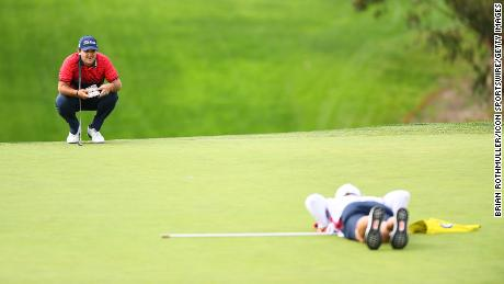 Reed and his caddie Kessler Karain line up a putt during the final round of the Farmers Insurance Open.
