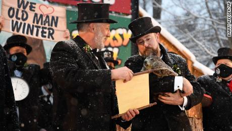 Groundhog Club handler A.J. Dereume holds Punxsutawney Phil, the weather prognosticating groundhog, as Vice President Tom Dunkel reads the scroll during the 135th celebration of Groundhog Day on Gobbler's Knob in Punxsutawney.