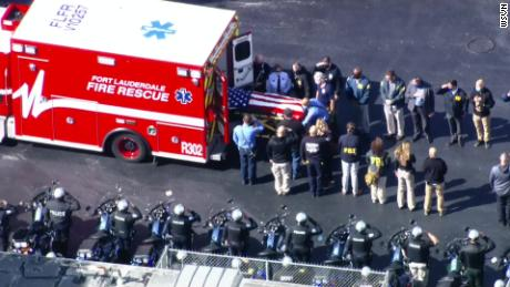 A body draped in an American flag is transported from an ambulance following the fatal shooting of two FBI agents in Sunrise Florida on Tuesday