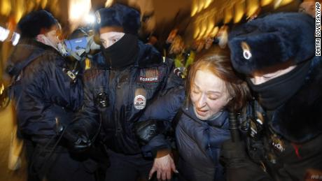 Police officers detain a Navalny supporter during a protest in St. Petersburg on Tuesday.