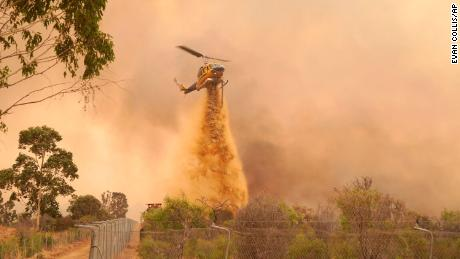 A helicopter drops fire retardant on a fire near Wooroloo, northeast of Perth, Australia, on February 2, 2021.
