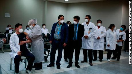ایک نرس بولیویا کے ال الٹو کے اسپتال ڈیل نورٹے میں COVID-19 کے خلاف ویکسینیشن منصوبے کے حصے کے طور پر پہلے ڈاکٹر کو اسپٹونک V کی ویکسین لگاتی ہے۔  (تصویر برائے گیسٹن برٹو / گیٹی امیجز)