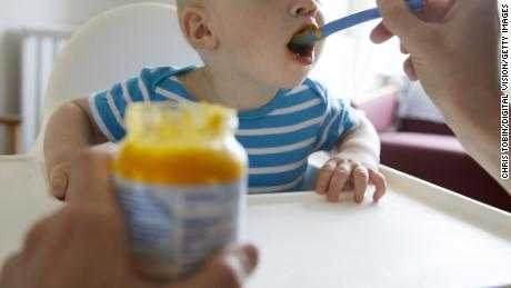 Baby taking a bite of food from a spoon with jar of baby food in foreground - stock photo