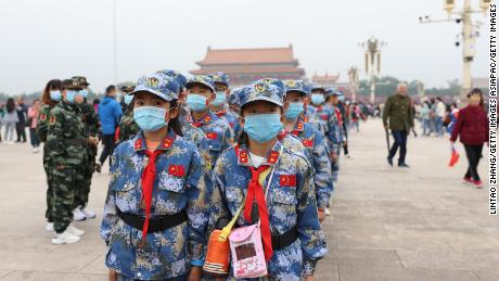 Chinese Young Pioneers wearing face masks take part in a flag-raising ceremony at Tiananmen Square on October 1, 2020 in Beijing, China.