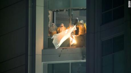 Detainees at City Justice Center in St. Louis hold flaming debris after escaping their cells and smashing windows.
