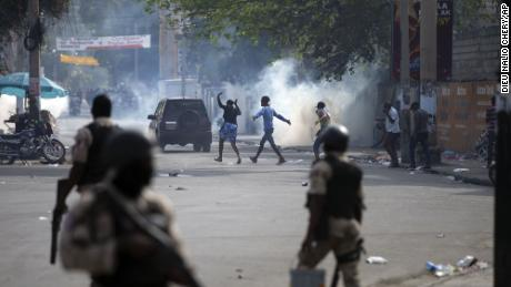 People walk across the street after the police fired tear gas during a nationwide strike demanding the resignation of Haitian President Jovenel Moise in Port-au-Prince, Haiti, 2 월 2.