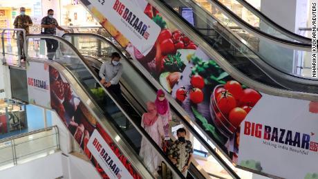 افرادی که در ماه نوامبر از فروشگاه Big Bazaar در بمبئی خارج می شوند.  Future Retail صاحب سوپرمارکت های زنجیره ای معروف است.