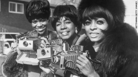 I Supremes (da sinistra a destra, Florence Ballard, Mary Wilson, and Diana Ross) pose with their cameras as they arrive at London Airport.