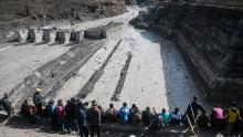 People look at the remains of a dam along a river in Tapovan of Chamoli district on February 9, 2021.