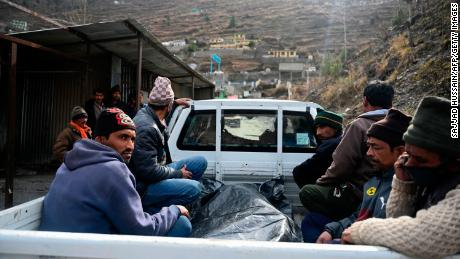 Relatives sit on the back a vehicle next to the body of a victim recovered from Raini village, outside a temporary morgue in Tapovan of Chamoli district on February 9, 2021.