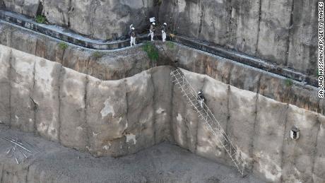 منگل کے روز لاپتہ کارکنوں کو تلاش کرنے کی امدادی کوششوں کے دوران ہندوستانی فوج کے اہلکار تپوان ڈیم میں عارضی سیڑھی پر چڑھ گئے۔