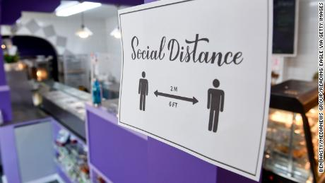 At Marisol's Bakery and Cafe in Pennsylvania, a sign asks people to social distance on October 6, 2020. Some Americans view returning to life as normal now as a moderate-level risk, a new poll has found.