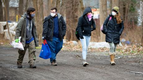 A resident, links, of the homeless encampment known as the Jungle, walks with Matt Dankanich, a community health worker for REACH Medical; a friend of the resident and Deb Wilke, reg, the homeless crisis alleviation coordinator for Second Wind Cottages, accompany them.