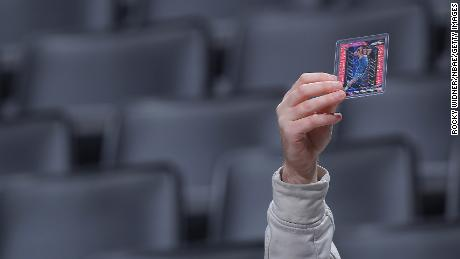 A fan holds up trading cards of Minnesota Timberwolves players prior to a game on Feb. 3, 2020.