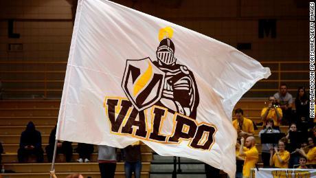 A Valparaiso University cheerleader waves a Valparaiso Crusaders flag.