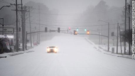 A car drives slow during the snowfall near Old Canton Road in Ridgeland, Mississippi on February 15, 2021.
