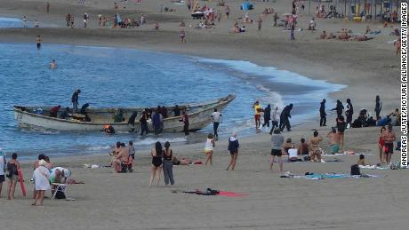 Refugees in an open boat land between sunbathing tourists on the beach at Los Cristianos, on December 10, 2020.