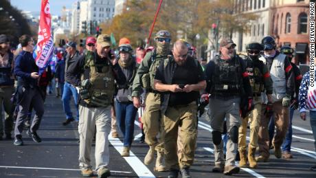 Rhodes, center in eye patch, marches with Oath Keepers through Washington, DC last November. Watkins is visible behind him to his right, wearing jeans and goggles on her ballistic helmet.
