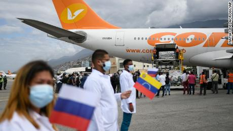 Healthcare workers hold national flags from Venezuela and Russia as workers unload a shipment of the Russian COVID-19 vaccine Sputnik V, at the Simon Bolivar International Airport in Maiquetia, Venezuela, 土曜日, Feb. 13, 2021.