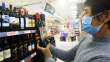 A customer looks at a bottle of wine imported from Australia at a supermarket on November 27 in Hangzhou, Zhejiang Province of China.