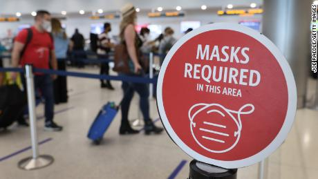 A sign reading, 'masks required in this area,' is seen at the Miami International Airport.