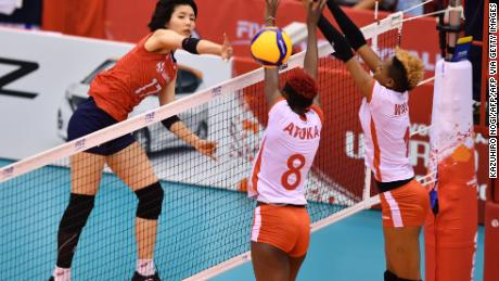 South Korea's Lee Da-yeong, 左, spikes the ball over Kenya's Trizah Atuka, center, and Jane Wacu Wairimu, right, during a match of the FIVB Women's World Cup volleyball between South Korea and Kenya in Osaka on September 27, 2019.