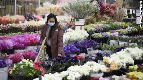 A customer wears a face mask while shopping for flowers on February 12, 2021 in Los Angeles, California