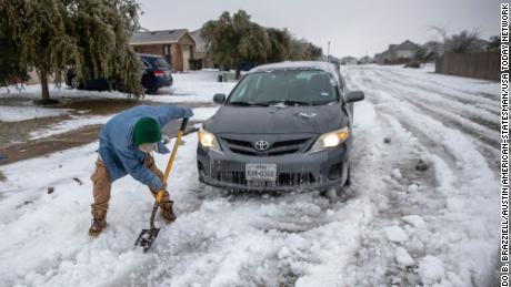 Jose' Nives tries to shovel his way out after getting stuck in the middle of the street.