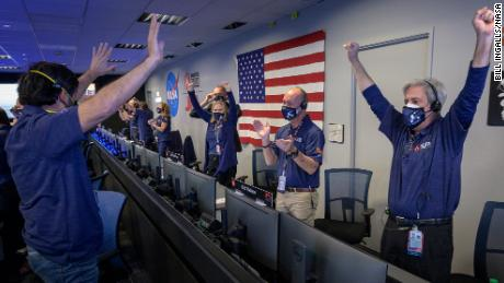 Members of NASA's Perseverance rover team react in mission control after receiving confirmation the spacecraft successfully touched down on Mars, Thursday, Feb. 18, 2021, at NASA's Jet Propulsion Laboratory in Pasadena, California. A key objective for Perseverance's mission on Mars is astrobiology, including the search for signs of ancient microbial life. The rover will characterize the planet's geology and past climate, pave the way for human exploration of the Red Planet, and be the first mission to collect and cache Martian rock and regolith. Photo Credit: (NASA/Bill Ingalls)
