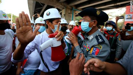 A protester speaks to a police officer during an anti-coup rally outside the Hledan Centre in Yangon, Myanmar on February 19.