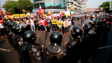 Anti-coup protesters face a row of riot police in Yangon on February 19.
