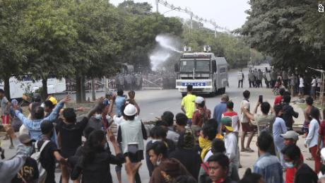 A police truck uses a water cannon to disperse protesters in Mandalay on Saturday