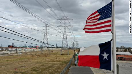 The U.S. and Texas flags fly in front of high voltage transmission towers on February 21, 2021 in Houston, Texas. Millions of Texans lost power when winter storm Uri hit the state and knocked out coal, natural gas and nuclear plants that were unprepared for the freezing temperatures brought on by the storm. Wind turbines that provide an estimated 24 percent of energy to the state became inoperable when they froze. (Photo by Justin Sullivan/Getty Images)