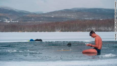 Czech freediver David Vencl rests on the icy Barbora lake near Teplice city, Czech Republic, on February 13, 2021 after his training to break the Guinness world record for the longest swim under ice.
