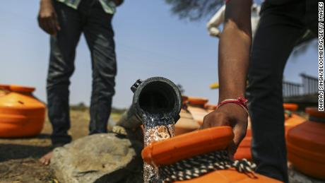 Water commuters fill containers at a groundwater source in Latur, Maharashtra, India, in 2016.