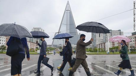 People walk in the rain in Pyongyang on May 15, 2020, wearing face masks amid the coronavirus pandemic.